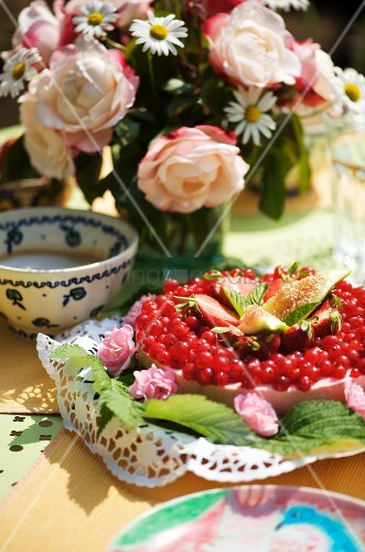 Johannisbeerkuchen auf und Blumenstrauss auf gedecktem Tisch im Freien