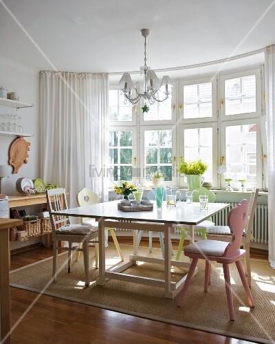 erker mit sprossenfenstern in sonniger wohnk che mit tisch vintage st hlen und einem teppich. Black Bedroom Furniture Sets. Home Design Ideas