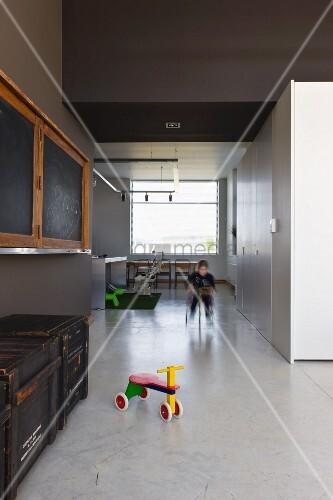 Puristischer Wohn/Essraum in umgenutztem Schulhaus; Spielzone auf poliertem Betonboden