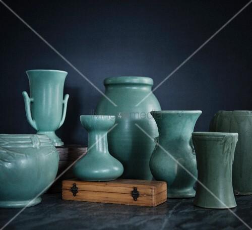 Range of different hand-thrown vases with light green glaze against black background
