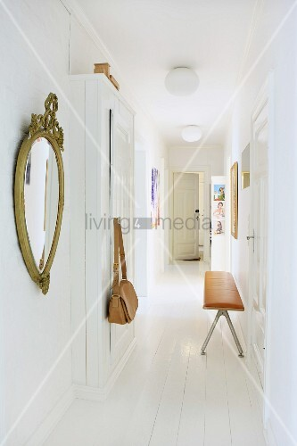 Fitted cupboard and white wooden floor in narrow hallway