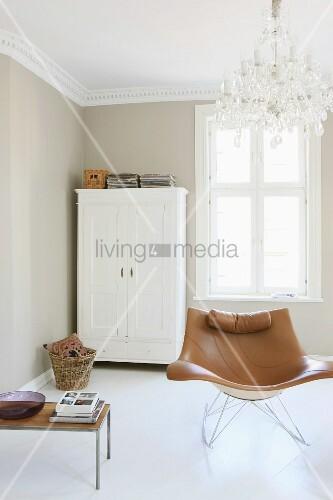 moderner sessel unter kronleuchter und weiss lackierter bauernschrank in renoviertem wohnraum. Black Bedroom Furniture Sets. Home Design Ideas
