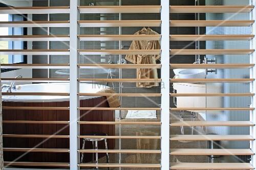 Raumteiler Lamellen blick durch raumteiler mit holzlamellen auf runde wellnesswanne in