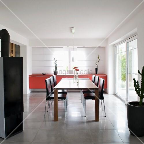 Moderner Esstisch und lederbezogene Stühle vor Sideboard mit roter Front am Fenster mit geschlossenen Flächenvorhängen