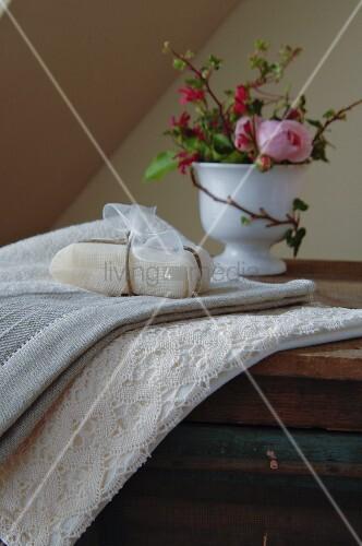 Wellness im romantischen Naturlook - Seifenpäckchen auf Handtuch und Spitzenbordüre, im Hintergrund Rose in Porzellanbecher