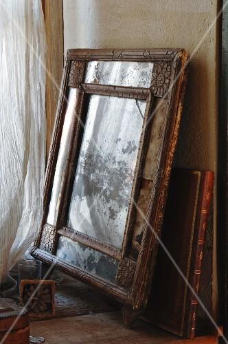 Alter Bilderrahmen mit Holzschnitzereien und Foliant mit goldgeprägtem Ledereinband an der Wand lehnend