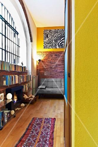 View through open door of corner of loft-style interior with ethnic runner on parquet floor and half-height shelving below industrial window