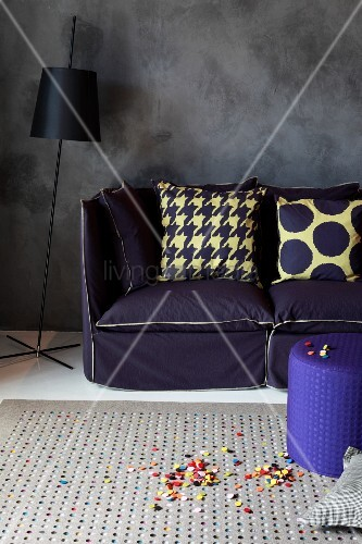 Scatter cushions on sofa with indigo upholstery and black standard lamp against dark grey wall