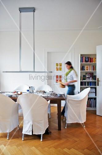Frau deckt den Tisch im modernen Speisezimmer
