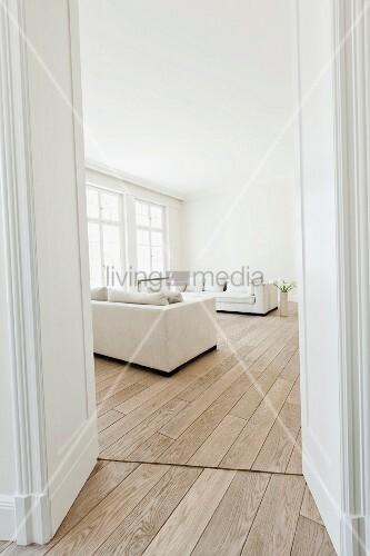 Moderner heller Wohnraum mit weißem Sofa und Holzboden, Fensterfront und Flügeltür