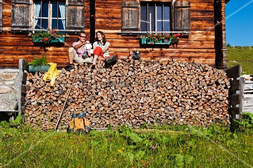 Couple sitting on stacked firewood in front of wooden house