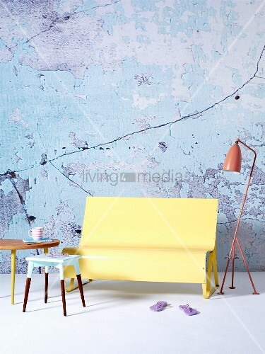 Fifties-style, painted occasional tables in front of yellow-painted bench and pink-painted standard lamp against wall with peeling paint