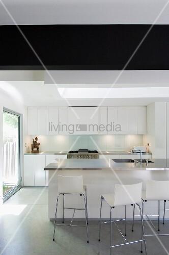 Barhocker Mit Lehne An Der Theke Einer Minimalistisch Weissen Küche Mit  Grossem Fenster Zum Sonnigen Garten