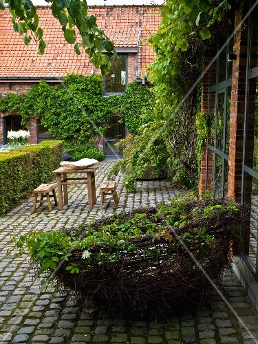 Large, decorative nest of willow whips in cobbled courtyard