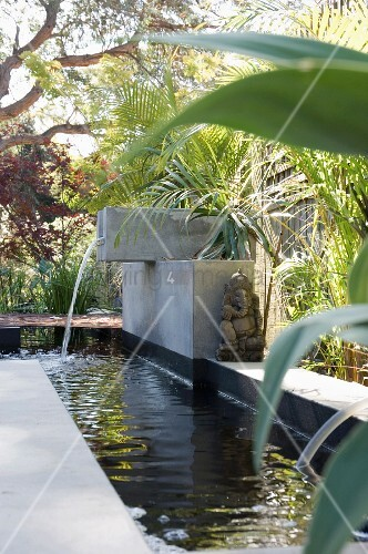 Ganesh sculpture on the edges of a rectangular water feature surrounded by palms