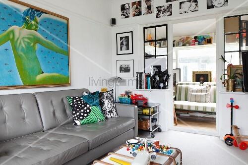 Graue Ledercouch unter modernem Bild an Wand eines Wohnzimmers und Blick durch offene Tür in Wintergarten