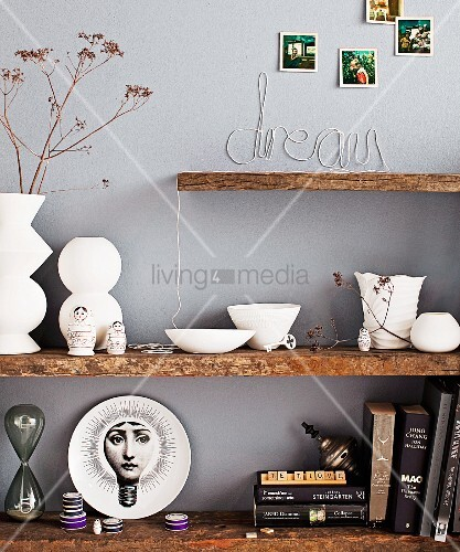 White ceramics, collection of ornaments and books on floating shelves made from rustic wooden boards