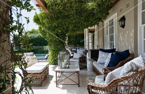 Grosse Terrasse mit berankter Pergola über Rattanmöbel vor traditionellem Landhaus