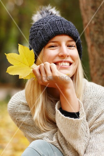 Woman holding yellow autumn leaf