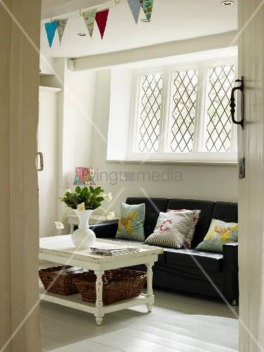Sofaecke mit schwarzem Ledersofa unter vergittertem Fenster, Tisch mit Blumenvase und bunter Wimpelkette