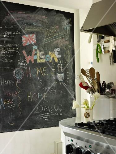 Beschriebene Schiefertafel und Küchenutensilien neben dem Herd in der Küche