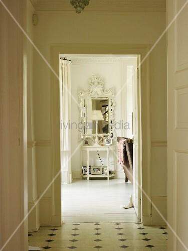 Blick durch eine Tür auf ein Wandtischchen mit Lampe und antikem Spiegel