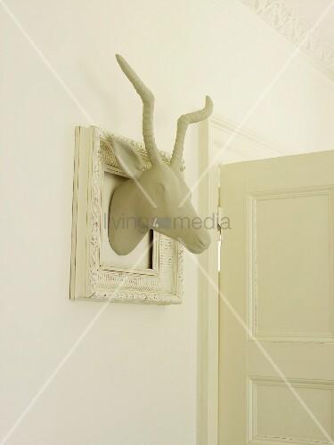 Weisser Gazellenkopf in einem weissen Bilderrahmen als Wanddeko