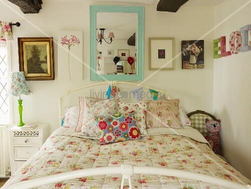 Romantisches Schlafzimmer mit Wandspiegel über dem Bett, Wimpelkette und Wandbildern