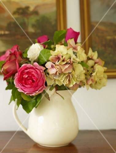 Sommerlicher Rosenstrauss mit Hortensienblüten in einer Krugvase vor Ölgemälden