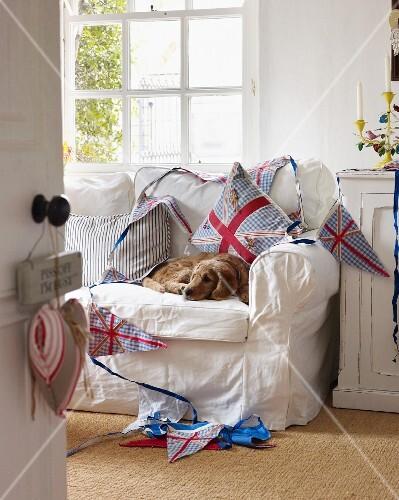 Hund auf weißem Sofa im gemütlichen Arbeitsraum mit Wimpelkette und bunten Kissen