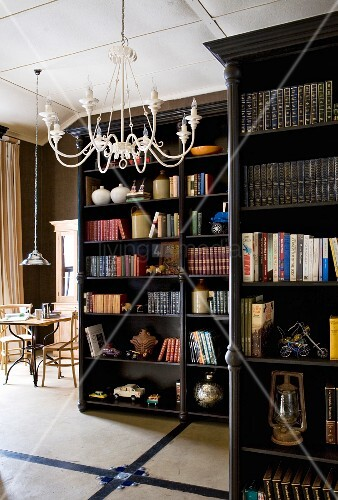 Dark, varnished, free-standing bookcases and white, metal chandelier on ceiling of open-plan living area