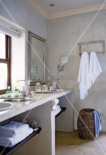 Stone washstand with twin basins, laundry basket and towels hanging on wall in bathroom