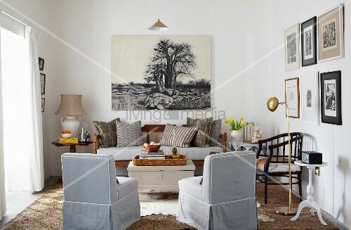 Wohnzimmer in Naturfarben mit antikem Holzsofa und darüber hängendem fotorealistischen Bild