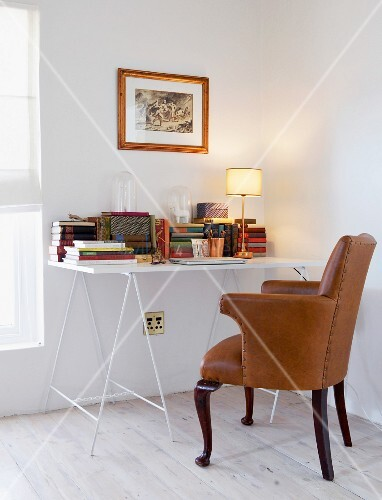 Simple desk on trestles and antique leather armchair in corner of white room