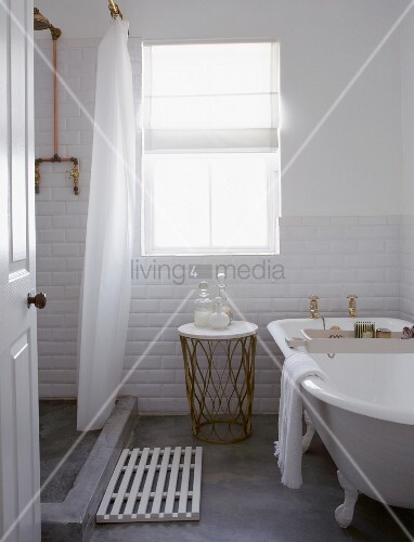 White-tiled bathroom with concrete floor, antique bathtub and shower area screened by shower curtain