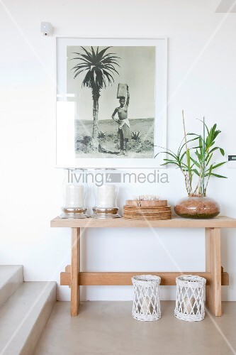 Framed black and white photograph above large lanterns and potted plant on simple console table