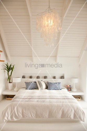 Comfortable, white double bed below white-painted wooden ceiling; lit, capiz shell pendant lamp hanging from sloping ceiling