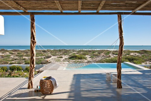 Calm, relaxing atmosphere on sunny, concrete terrace with infinity pool and view of horizon; mesh hammock hanging from two rustic, wooden supports in foreground