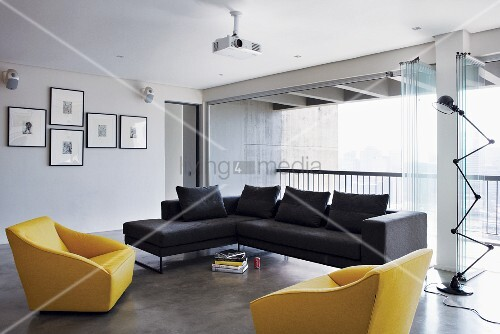 Helles, modernes Wohnzimmer mit gelben und blauen Sitzmöbeln und offenem Zugang zum Balkon durch ein offenes Faltfenster