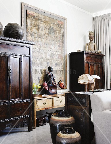 Hodgepodge of Chinese furniture and objets d'art from around the world in white interior with large, Chinese painting on wall