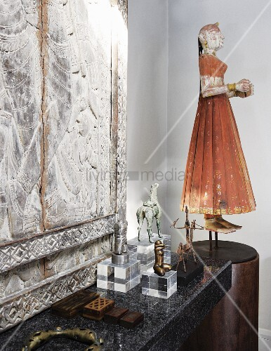 Chinese puppet of woman on pedestal and collection of statues on plexiglass plinths in front of stone relief on stone surface