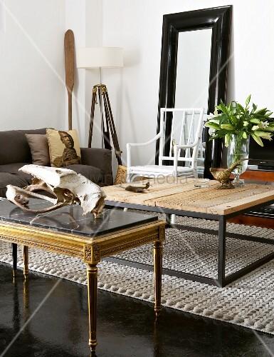 Wohnzimmer mit grauem Sofa, Holztisch, Beistelltisch mit Tierschädel, Holzstuhl, Spiegel und Stehlampe