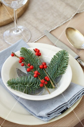 A Christmas place setting with fir branches and berries