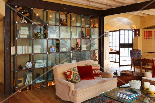 Two-seater couch with colourful scatter cushions in front of partition shelving with glass doors in open-plan interior