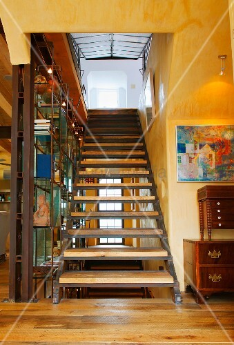 Modern, open staircase with wooden treads in yellow-painted interior with rustic ambiance
