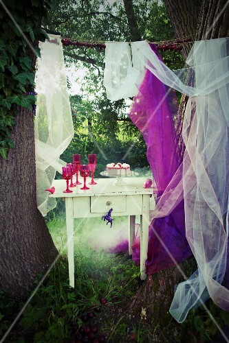 Raspberry cake on cake stand and pink glasses on vintage table between two large tree trunks in garden