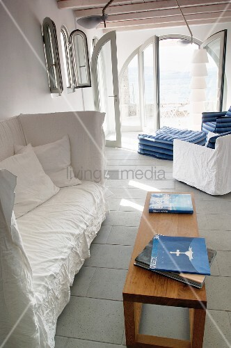 High-backed sofa with white loose cover in front of comfortable lounge area with ottoman and open terrace doors with sea view
