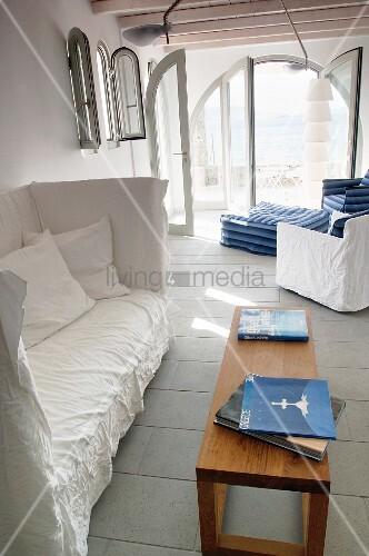 Sitzbank mit hoher Rückenlehne und weisser Husse vor gemütlicher Loungeecke mit Polsterhocker an offener Terrassentür mit Meerblick