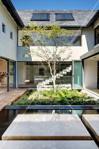 Window wall facing a home's protected courtyard; courtyard with planting bed and water feature