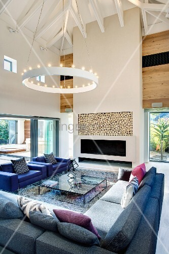 Large corner sofa and armchairs beneath a contemporary ring pendant light in a two story living room with hipped roof; ceiling height fireplace with firewood storage